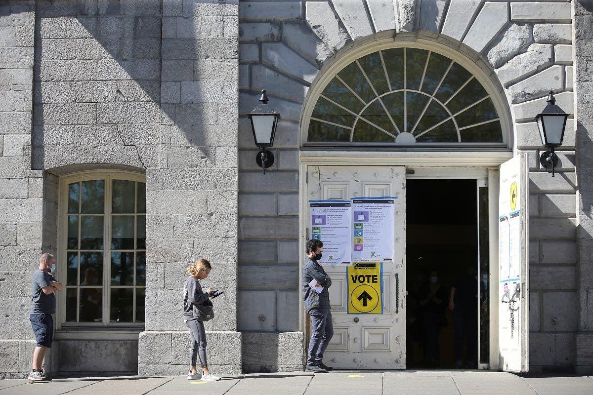 ناخبون ينتظرون خارج أحد مراكز الاقتراع بكندا (رويترز)